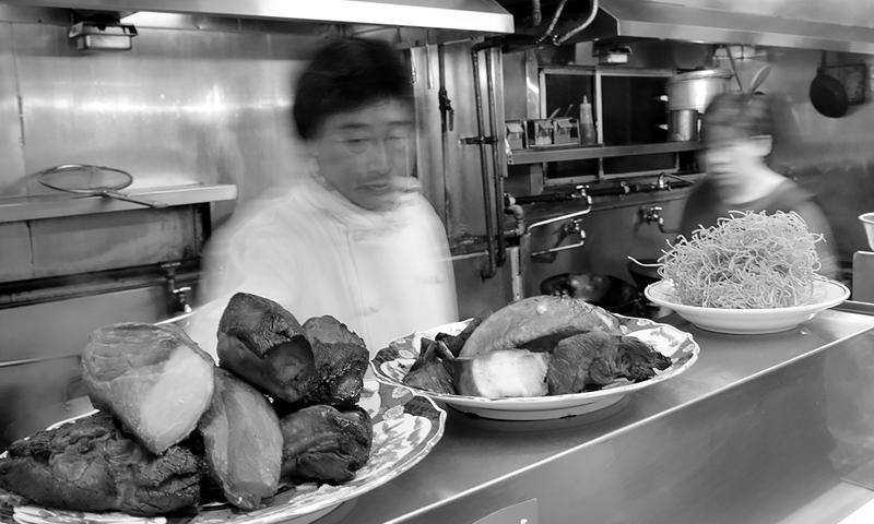 3代目の店主が厨房で調理する様子
